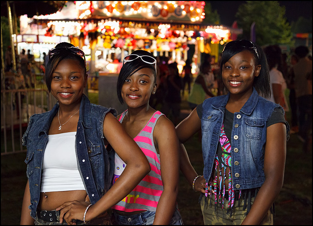 Three African-American teen girls at the Three Rivers Festival surrounded by the bright lights of the carnival rides.
