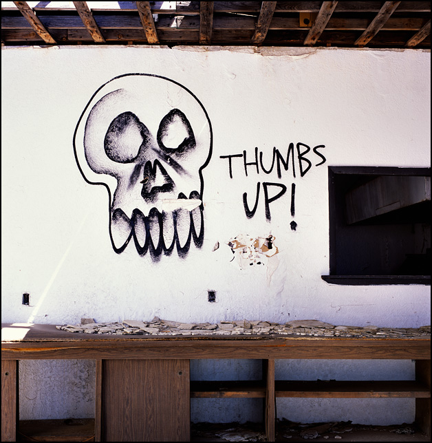 Graffiti of a skull and the words Thumbs Up spray painted inside an abandoned restaurant on Route 66 and I-40 in New Mexico.
