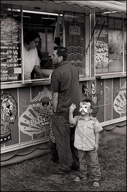 A young Asian boy wearing a tiger mask looks at his hand while he waits for his father to buy food at the funnel cake stand at the Three Rivers Festival carnival in Fort Wayne, Indiana.