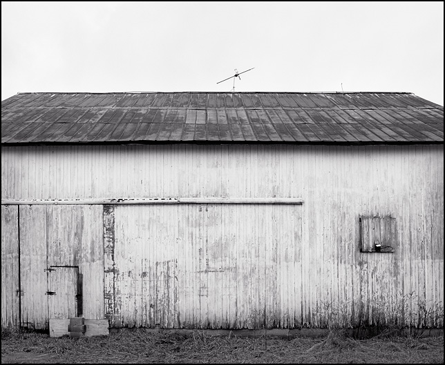 An old weathered whitewashed barn in rural Indiana with a basketball hoop and lightning rod.