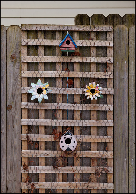 Four small metal birdhouses on a wooden trellis in front of a fence. Two of the birdhouses are shaped like flowers, one is shaped like a ladybug, and one looks like a normal birdhouse.