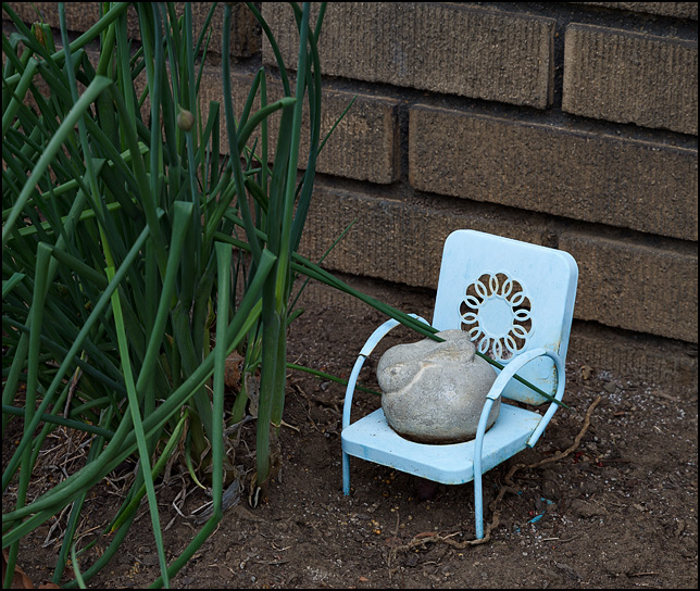A fat bunny carved from stone sits on a tiny replica of a vintage metal patio chair in the flowerbed behind a house in Fort Wayne, Indiana.