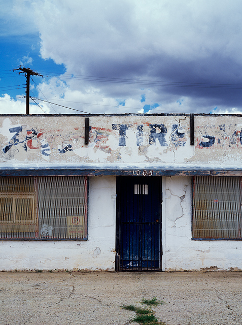 An abandoned tire shop on Route 66 in the small town of Tucamcari, New Mexico. The building is white adobe with metal grates over the windows. An old Route 66 sign sits in a window.