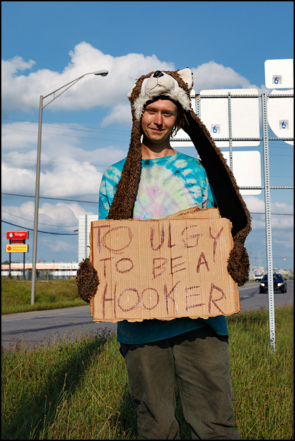 A young man wearing a wolf-head hat panhandling at the intersection of Coliseum Boulevard and Goshen Road US-33. He is holding a sign that says, Too Ugly To Be A Hooker.