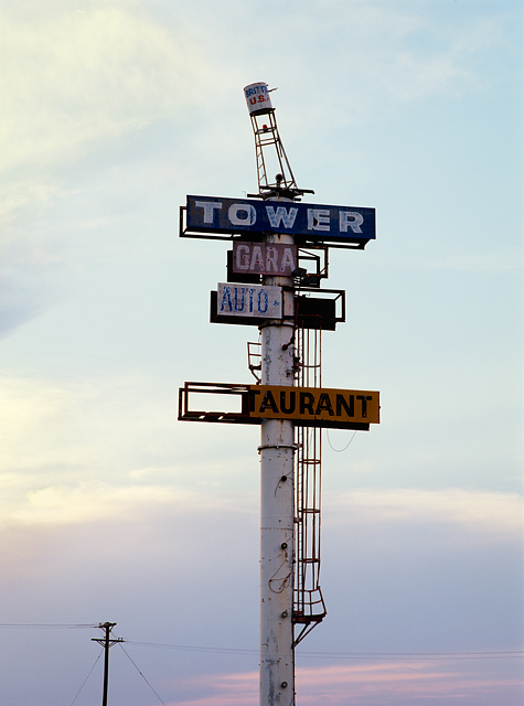 The sign for the abandoned Tower Garage and Restaurant next to the famous Britten USA leaning water tower outside Groom, Texas. It features a replica of the leaning tower on top of the signpost.