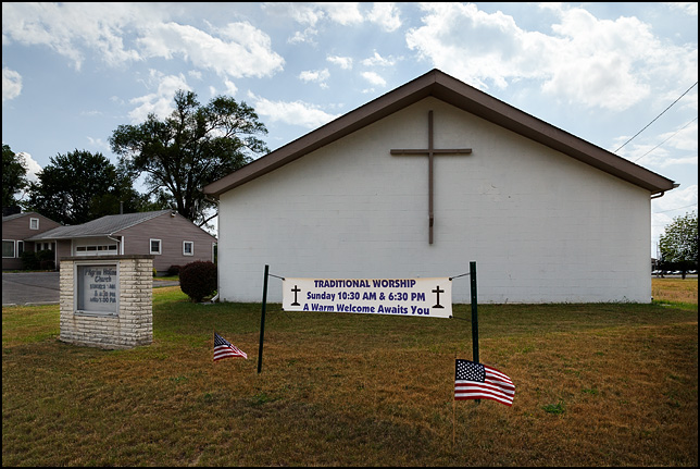 American flags flank a banner advertising traditional worship in front of Pilgrim Holiness Church in Fort Wayne, Indiana.