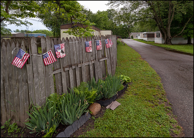 A string of metallic mylar American flags on a fence at the entrance to a trailer park on Sandpoint Road in Fort Wayne, Indiana.