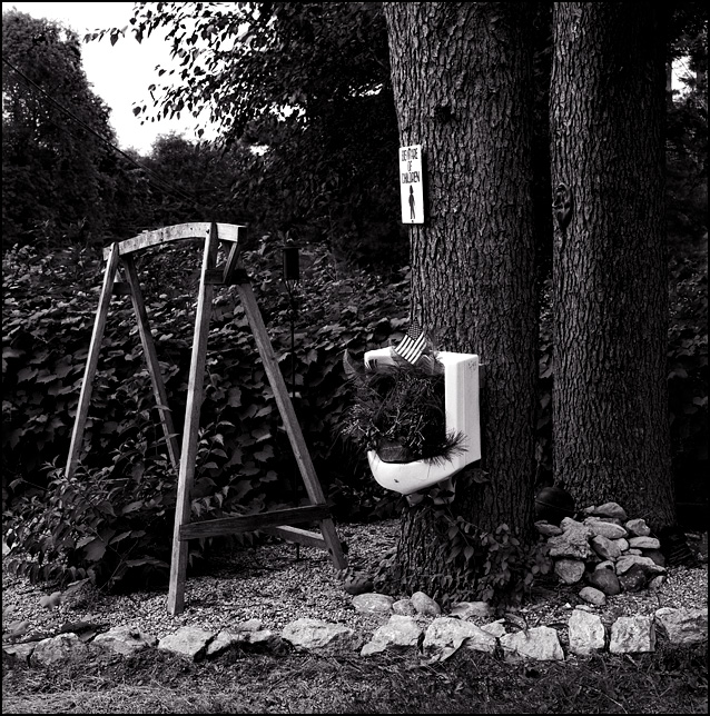 An old urinal with an American flag hanging on a tree in a front yard on Elmhurst Drive in Fort Wayne.