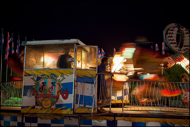 The brightly colored lights on the Orbiter carnival ride are a blur as the operator steps out of the control booth of the moving ride.