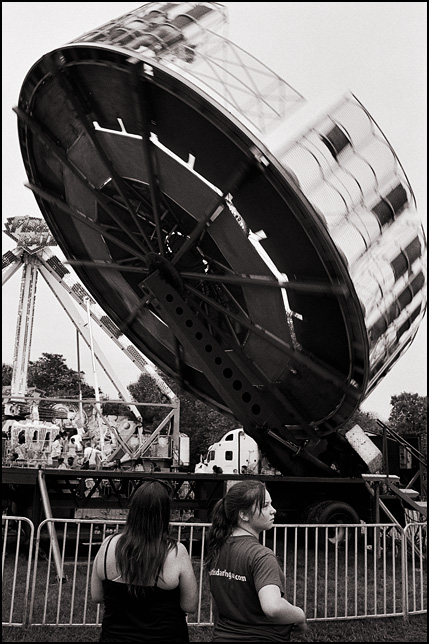 Two young women watch the Super Round-up ride as it spins almost vertically at the 2015 Three Rivers Festival in Fort Wayne, Indiana.