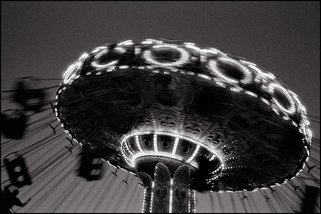 A brightly lit Swing Carousel ride is a spinning blur of motion at a night time carnival.
