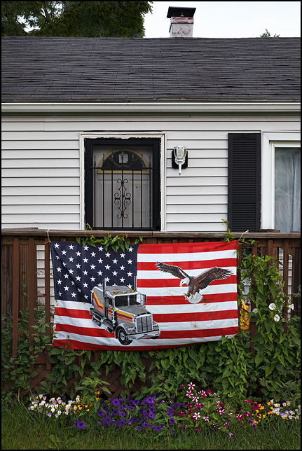 An American flag with a bald eagle and a semi truck printed on it hangs on the front porch of a house on Paulding Road in Fort Wayne, Indiana.