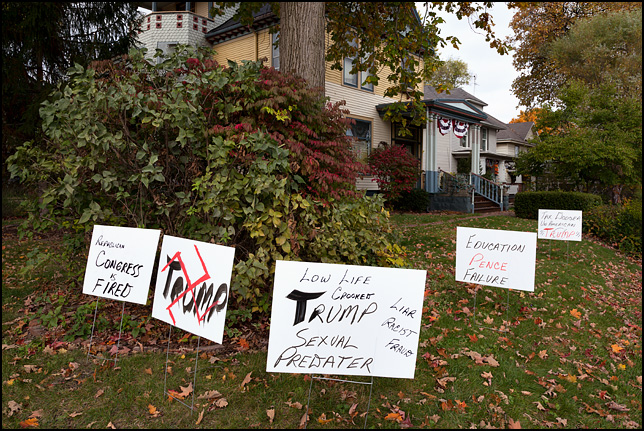 Several anti-Donald Trump signs in front of a victorian house on Wells Street in Fort Wayne, Indiana. LowlifeTrump Crooked Sexual Predator. Liar, Fascist, Fraud. Republican congress is fired. Tax Dodger Trump. Education Pence Failure. One sign has a red swastika drawn over it.