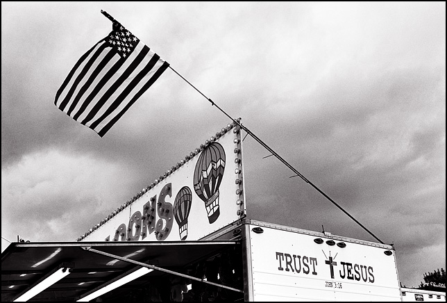 A carnival game trailer that has Trust Jesus and a cross painted on the end of it and has an American flag flying from the awning.