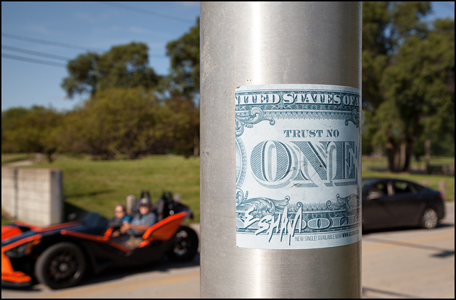 A sticker that looks like the back of a one dollar bill on a light pole in downtown Fort Wayne, Indiana. The sticker says Trust No One.