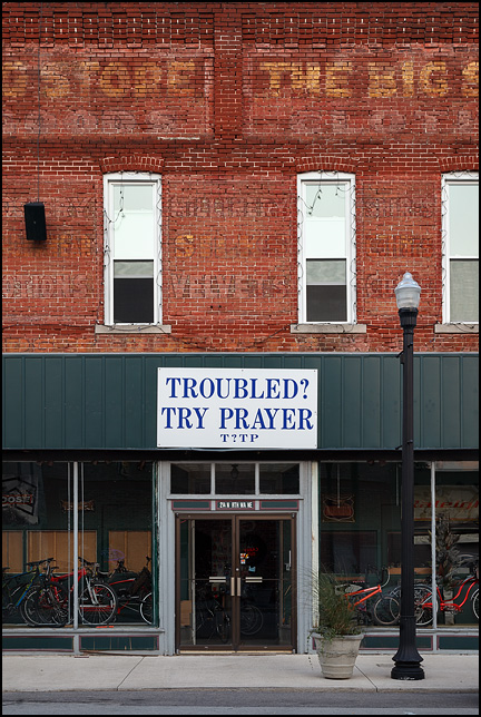A large religious sign above the front door of a bicycle shop in the small town of Warren, Indiana. The sign encourages troubled people to Try Prayer. Faded signs for a dry goods store are still visible on the brick facade of the old building.