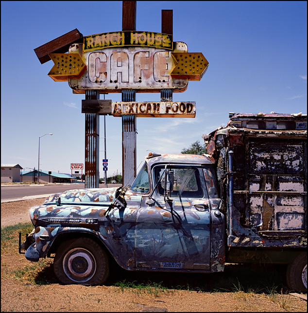 An old beat-up Chevrolet pickup truck with a homemade camper shell sits in front of a sign for the abandoned Ranch House Cafe Mexican Restaurant on Route 66 in Tucamcari, New Mexico.