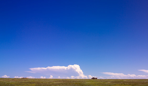 A tiny house on the horizon under a big blue sky on the plains along the Turquoise Trail south of Santa Fe, New Mexico.