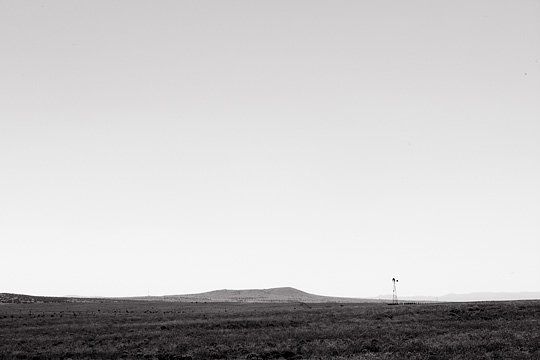 An old windmill and a low hill on an abandoned ranch on the plains south of Santa Fe, New Mexico.