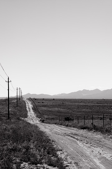 A dirt road runs alongside New Mexico Highway 14 through an empty high plains landscape under a big sky toward the Ortiz Mountains along the Turquoise Trail.