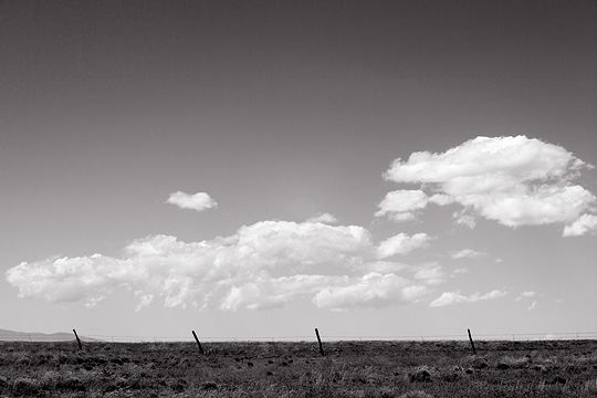 Barbed wire fence under a big sky on the high desert plains of New Mexico along the Turquoise Trail.