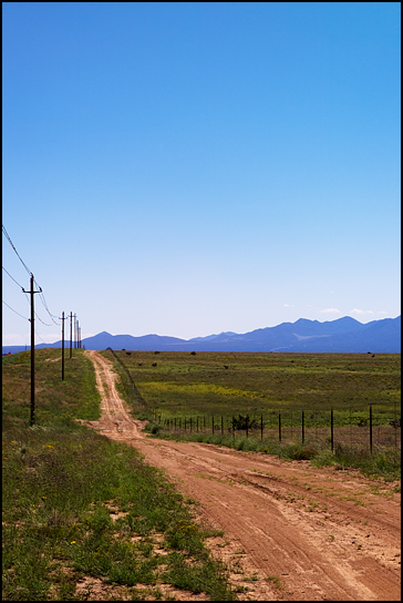 A dirt road runs alongside New Mexico Highway 14 through an empty high plains landscape under a big blue cloudless sky toward the Ortiz Mountains along the Turquoise Trail.