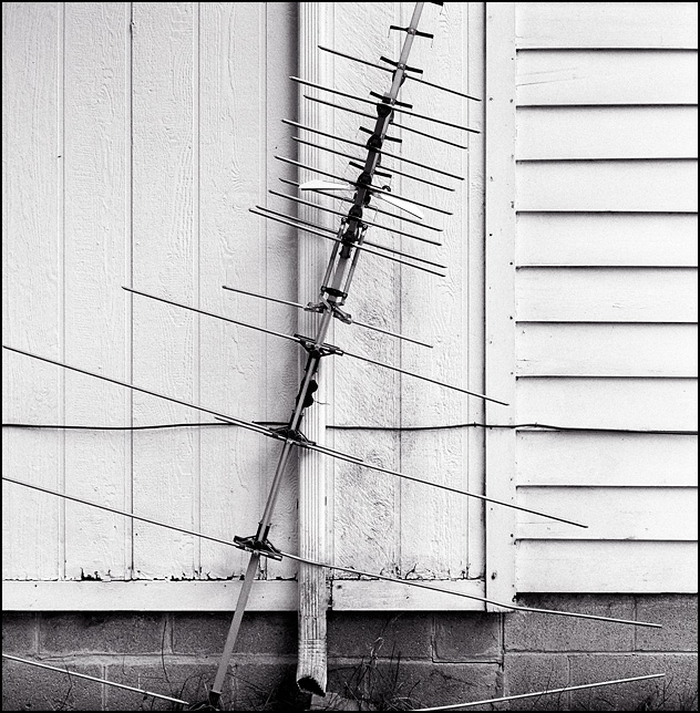 A large analogue television antenna leaning against the side of an old house.
