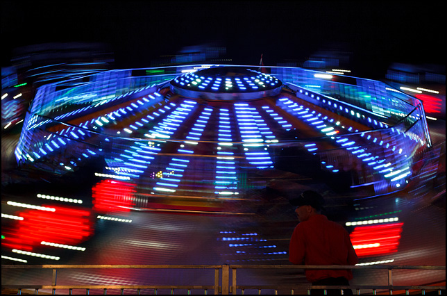 The Twister ride spins in a circle of colorful blue and red lights in the dark at the 2016 Elkhart County Fair in Goshen, Indiana.