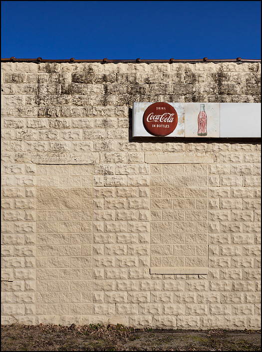 An old Coca Cola sign on the side of an abandoned gas station in the small town of Tyner, Indiana. The door and window on this side of the building have been bricked up with cement blocks.