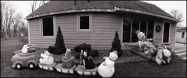 Inflatable Santa Claus with snowmen and a penguin and inflatable Winnie the Pooh characters in front of a house on Tyrone Road in Fort Wayne, Indiana.