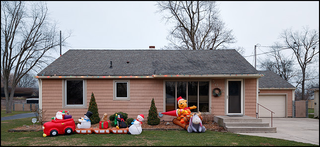 Inflatable Santa Claus in a car with snowmen and a penguin and inflatable Winnie the Pooh Christmas holiday decorations in the front yard of a house on Tyrone Road in Fort Wayne, Indiana.