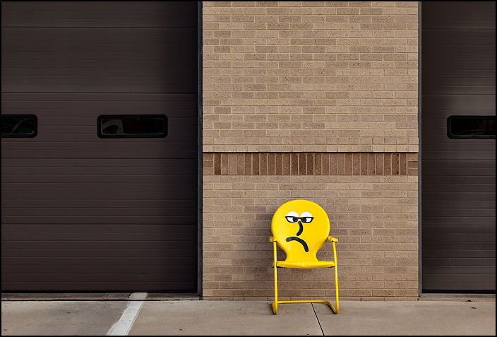 A yellow metal motel chair with a frowning face emoji painted on it sits in front of Fire Station 10 at the corner of Crescent and Anthony in Fort Wayne, Indiana.