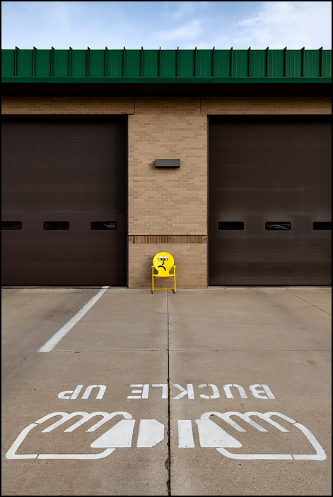 A graphic of hands buckling a seatbelt and the words BUCKLE UP are painted on the driveway in front of Fire Station 10 at the corner of Crescent and Anthony in Fort Wayne, Indiana. A yellow metal motel chair with a frowning face painted on it sits in front of the firehouse.