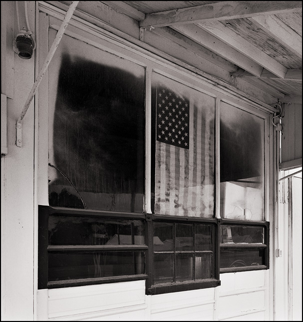 A large faded paper American flag hangs in the front window of an old auto repair shop in Uniondale, Indiana.
