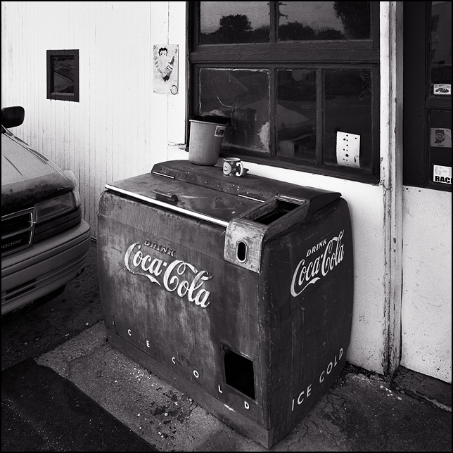 Antique Coca-Cola icebox in front of an old auto repair garage in Uniondale, Indiana.