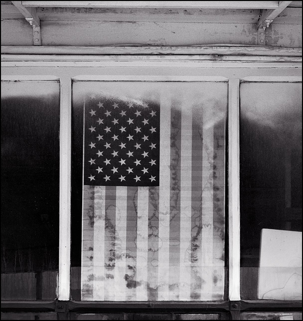 A faded paper American flag covered in mildew hangs in the front window of a small town auto repair shop in Uniondale, Indiana.