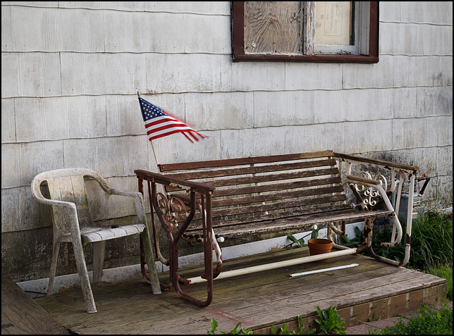 An American flag flies from the back of a glider swing that sits next to a dirty plastic patio chair behind an old building in Uniondale, Indiana.
