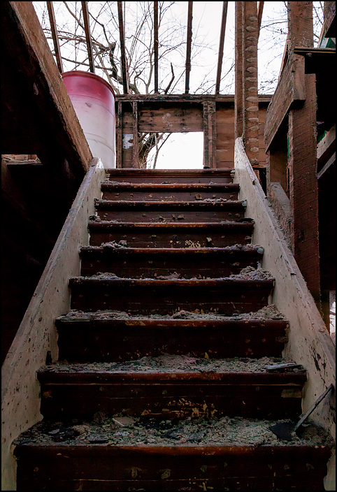 The stairway inside an abandoned farmhouse that is being demolished. The roof has been torn off, so the second floor is open to the sky. The house is on Lower Huntington Road in rural Allen County, Indiana.