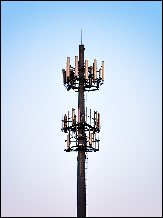 A cellphone tower at dusk. The tower is a steel pole on US-33 on the northwest side of Fort Wayne, Indiana.