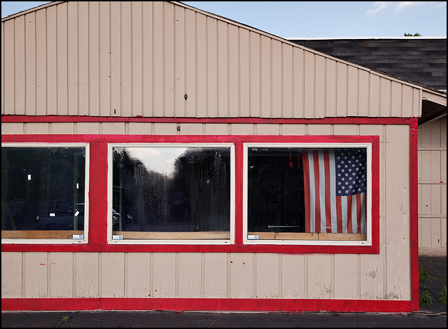 An American flag hangs in one of the front windows of a vacant storefront at the corner of Broadway and Huestis Avenue in Fort Wayne, Indiana.