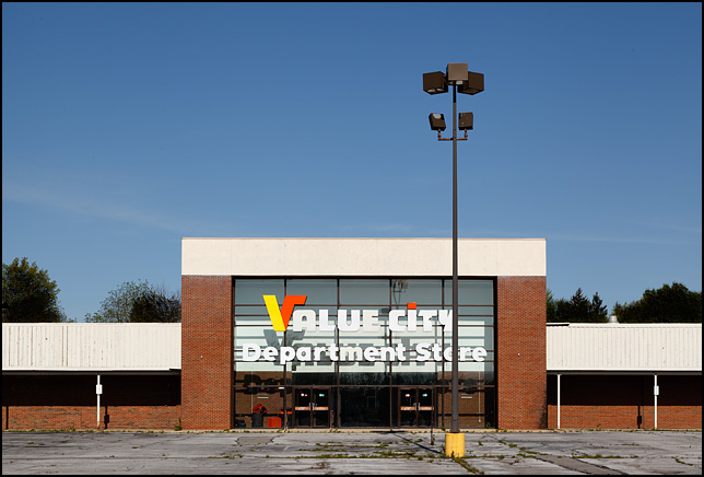 An abandoned Value City Department Store sits in a crumbling parking lot in Fort Wayne, Indiana.