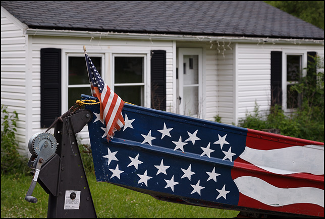 A rowboat painted like the American flag sits on a trailer in front of a house in the small town of Van Buren, Indiana. A small American flag flies from the bow of the boat.