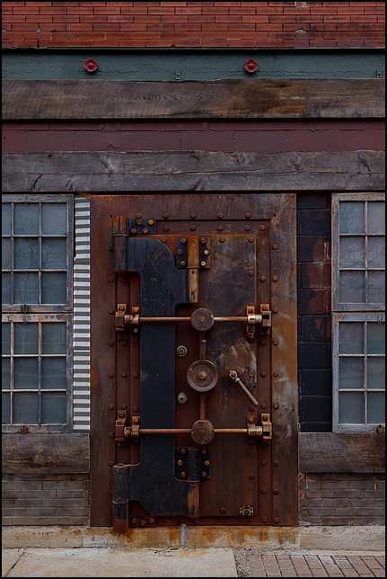 An old bank vault door installed as the main entrance to a brick storefront building on College Avenue in Indianapolis.