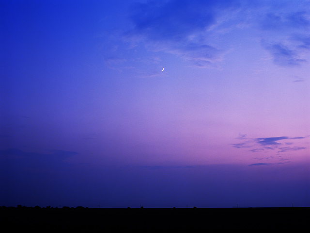 The crescent moon is visible in the blue and purple sky at sunset over the plains near Vega, Texas.