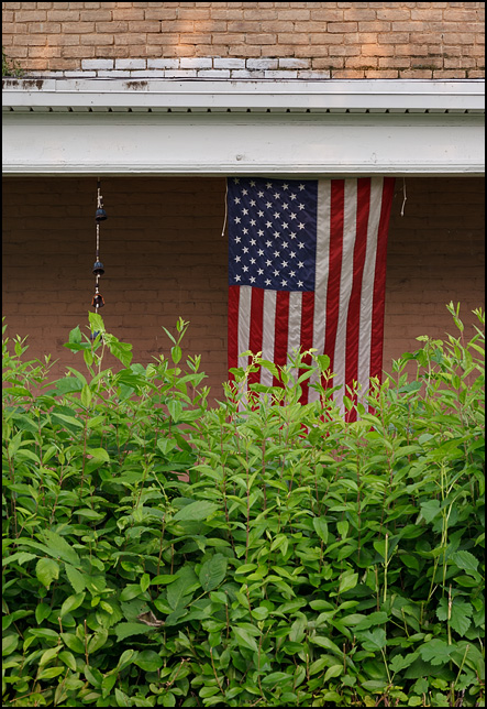 An American flag hanging on the veranda of an old brick house behind a tall hedge at the corner of Boone Street and Mechanic Street in Fort Wayne, Indiana.