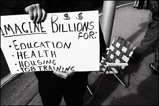 A peace activist in Santa Fe holds a sign that says Imagine Billions for Health, Education, Housing, Job Training.