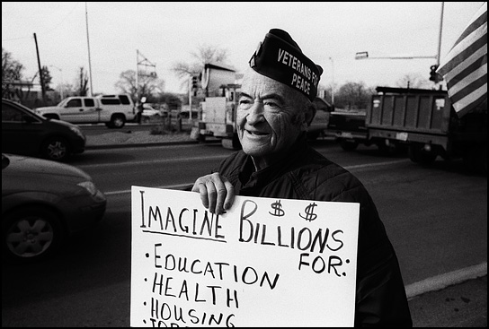 A World War II veteran from the antiwar group Veterans For Peace holds a sign that says Imagine Billions for Health, Education, Housing, Job Training.