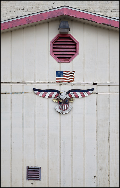A painted metal American flag and wooden bald eagle on the front of Victory Lanes bowling alley in the small town of Gas City, Indiana.