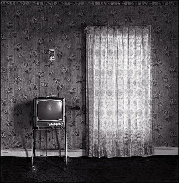 An old General Electric television set sits on a stand next to the window in an abandoned farmhouse. The wall behind the TV is covered in floral wallpaper.