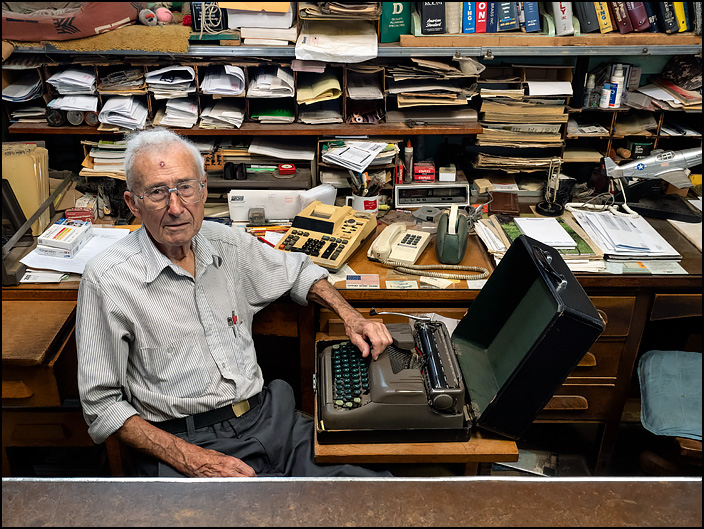 Virgil Hoke, the 84 year old owner of Waynedale Plumbing Supply, sits behind the counter of the store on Lower Huntington Road in Fort Wayne, Indiana. The desk is cluttered with old paperwork and an old manual typewriter sits on a table in front of Virgil.